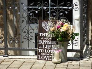 Dekoration im Hof mit Blumen, Schild und Windlicht