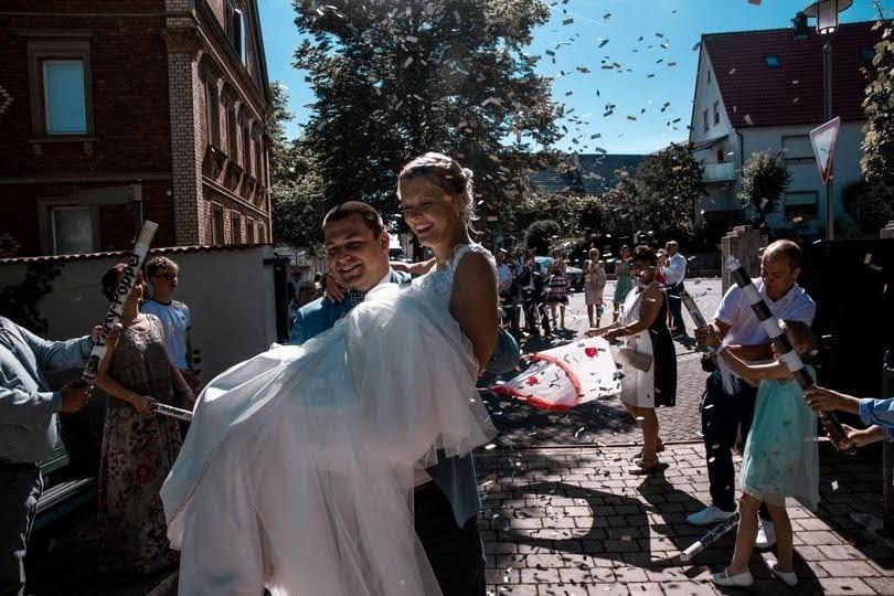 Bräutigam trägt Braut durch Konfettiregen