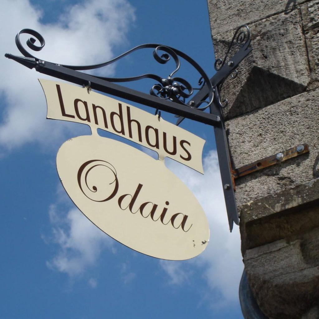 Das Schild vom Landhaus Odaia am Eck des Hauses vor blauem Himmel