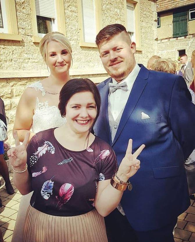 Brautpaar lacht in die Kamera während Gast davor steht und lachend ein Peace-Zeichen mit den Händen hält