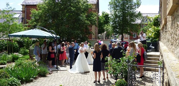 Brautpaar und Gäste neben Sekt im Hof zu sich