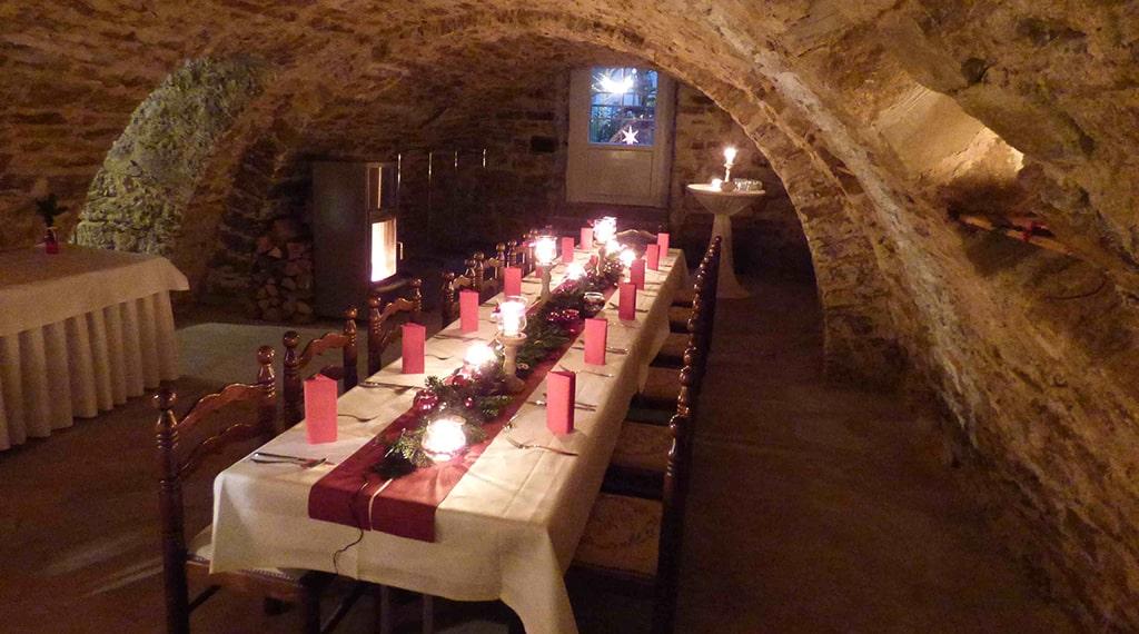 in rot dekorierte Festtafel mit Kerzen in beleuchteten Gewölbekeller