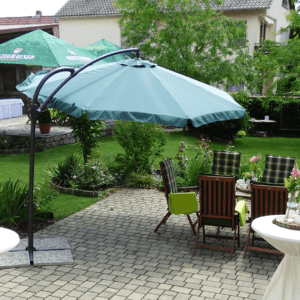 grüner Garten mit Sonnenschirmen und Gartensitzgelegenheiten
