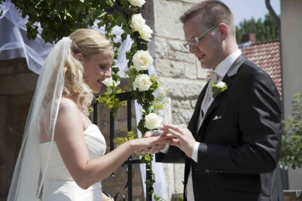 Bräutigam steckt Braut den Ehering an