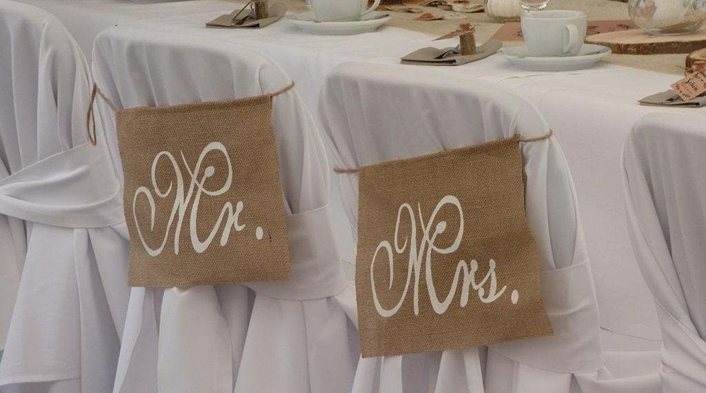 Das frischvermählte Ehepaar sitzt auf den Stühlen mit Schild Mr. & Mrs.