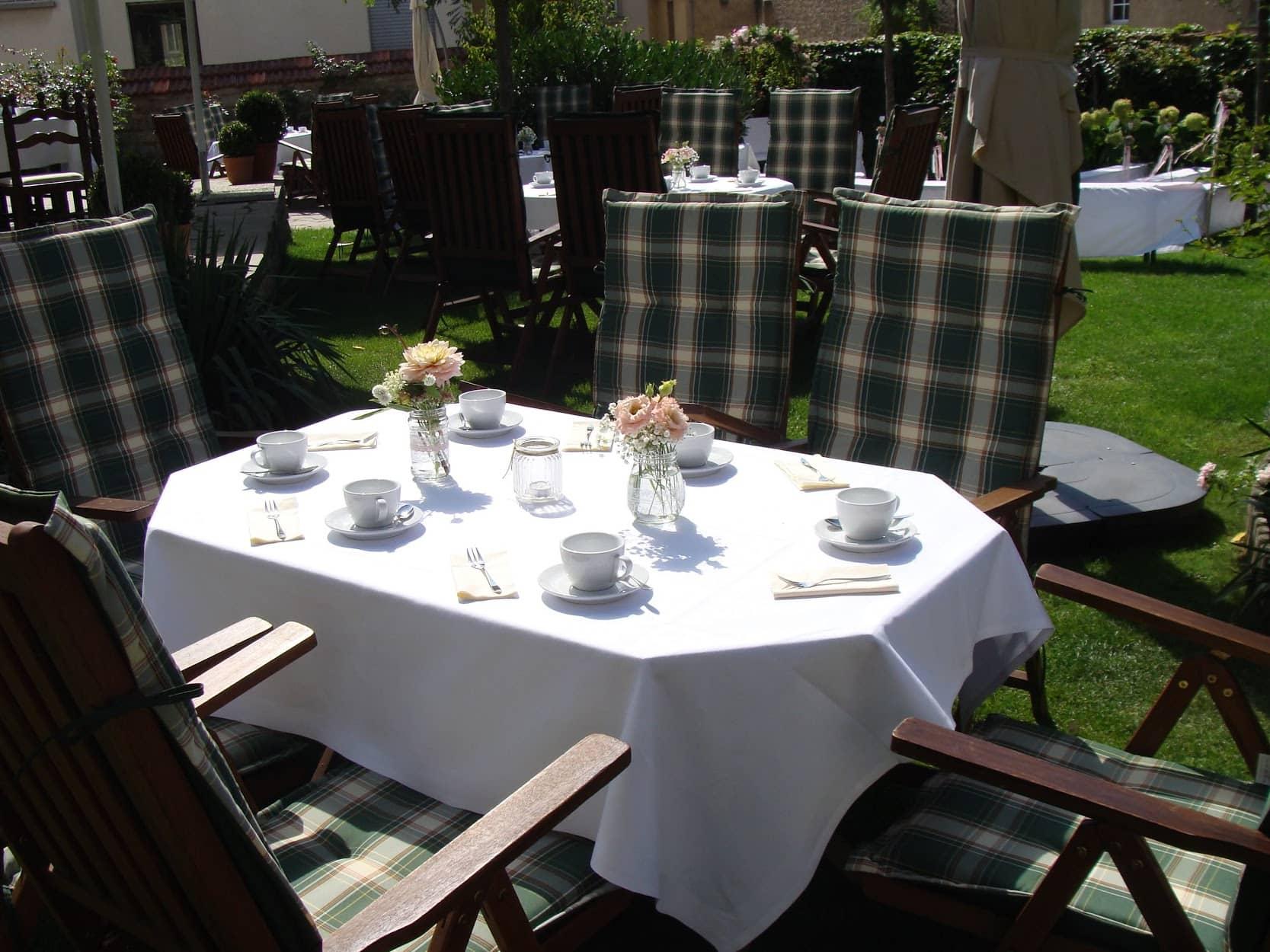 für Kaffee und Kuchen hergerichtete Tische im Garten