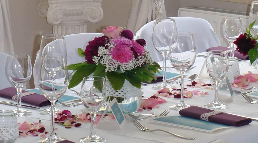 Tafel wurde mit Menükarten in lila und rosa Blumengesteck eingedeckt