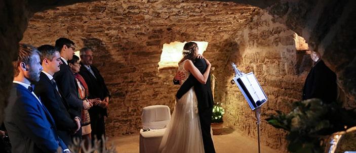 frisch getrautes Ehepaar umarmt sich bei freier Trauung im Gewölbekeller