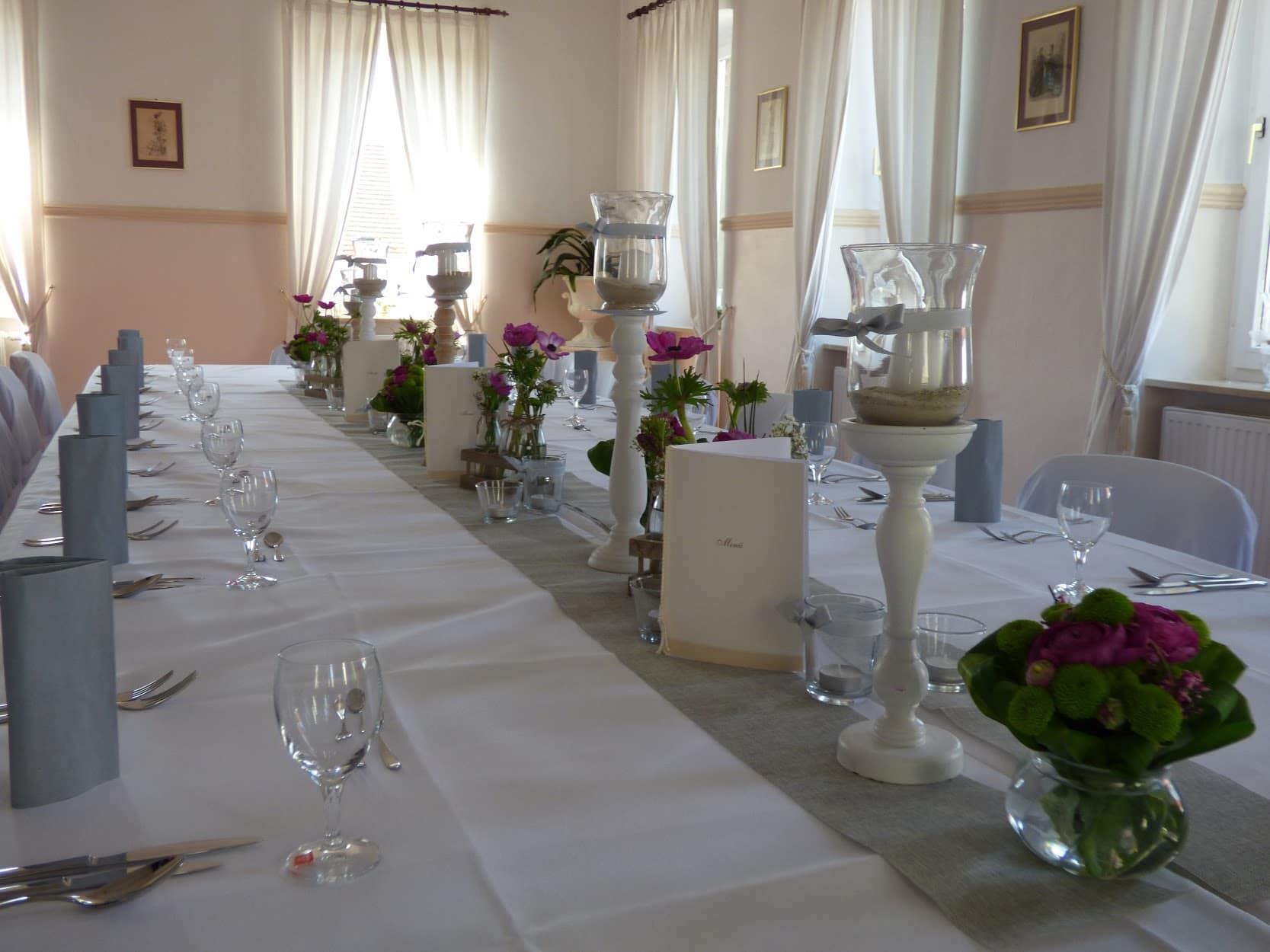 gedeckte Geburtstagstafel mit blauen Servietten, Menükarten und Blumenschmuck