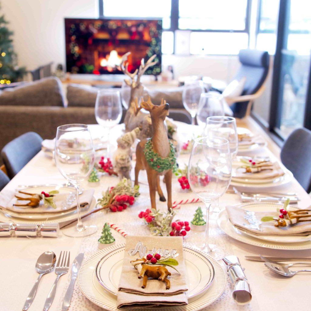 Weihnachtliche geschmückte Tafel mit Hirschen in der Mitte vor Kamin und Weihnachtsbaum