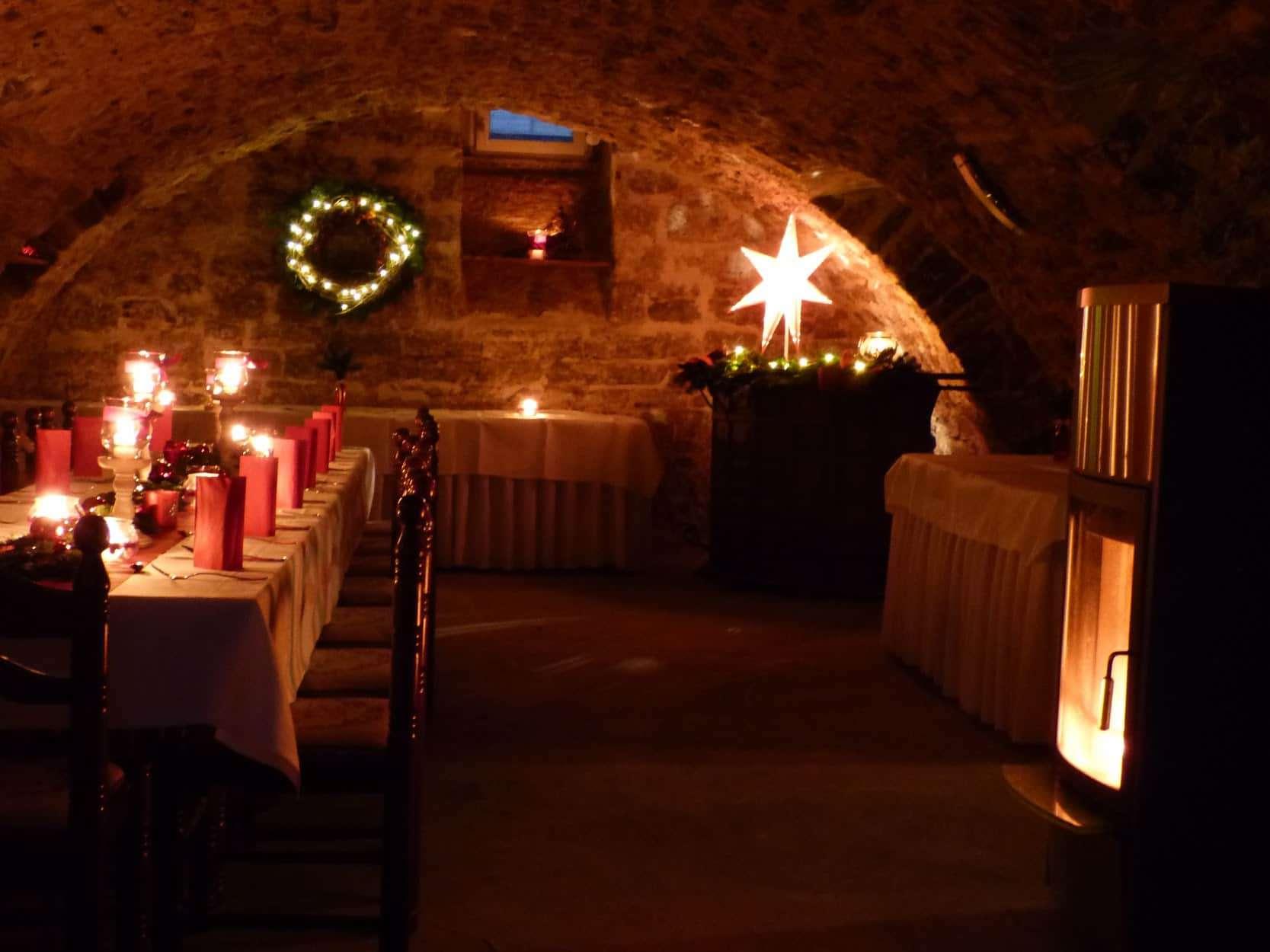 weihnachtlich dekorierter Gewölbekeller mit Festtafel