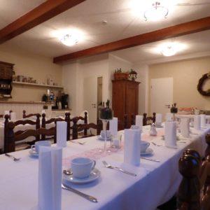 Zwei für den Kaffeetisch gedeckte Tafeln in einem Raum mit kleiner Küchenzeile zum Anrichten von Speisen