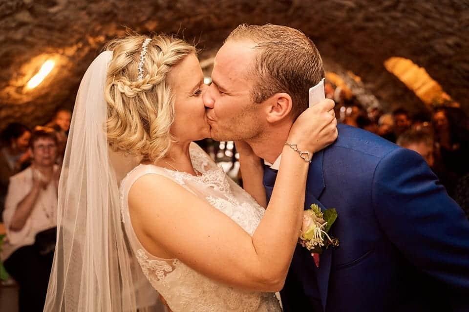 das Ehepaar küsst sich nach der Trauung im Gewölbekeller