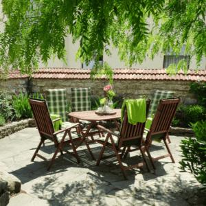 Tisch im Garten mit Blumen dekoriert und Stühlen mit Sitzpolster und Decken