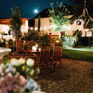 mit Lichterketten beleuchteter Hof und Garten bei Nacht