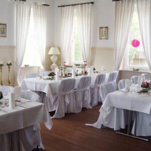 drei Tische sind für das Event mit Blumen und Geschirr gedeckt