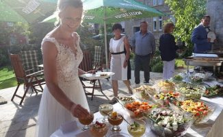 Braut bedient sich am kalten Buffet im Hof