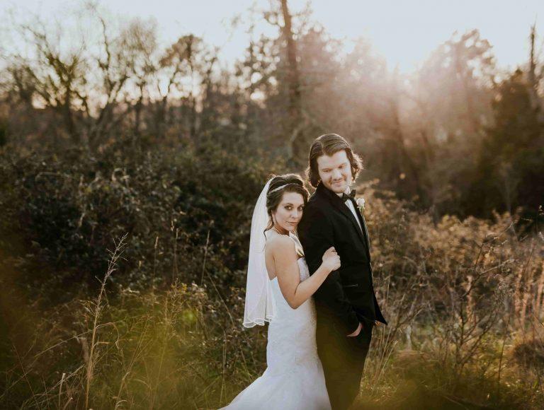 Braut umarmt Bräutigam von hinten während sie vor grüner Winterlandschaft posieren