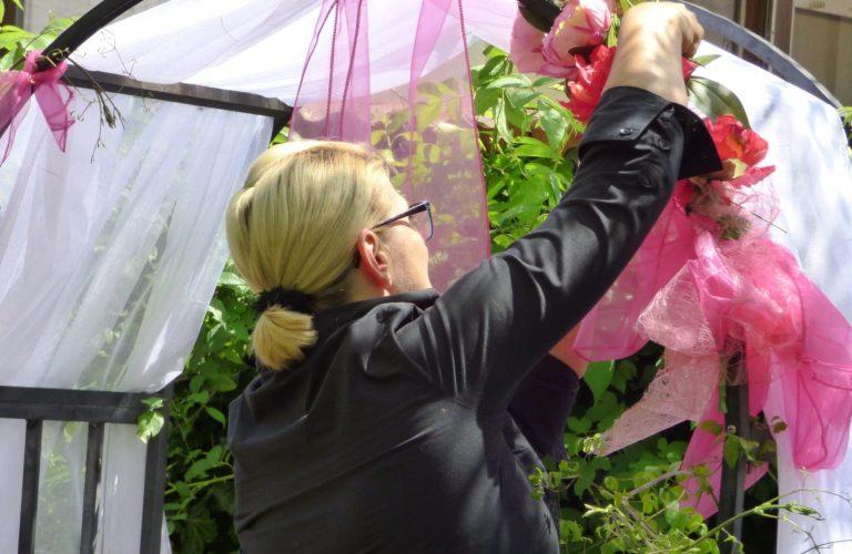 Bogen für Hochzeitsdekoration wird von Floristin mit rosa Blumen geschmückt