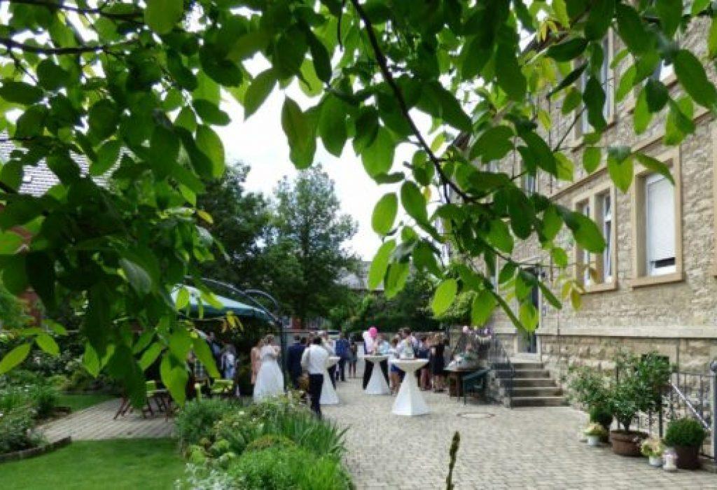 Blick auf Hof und Garten mit Stehtischen für Empfang