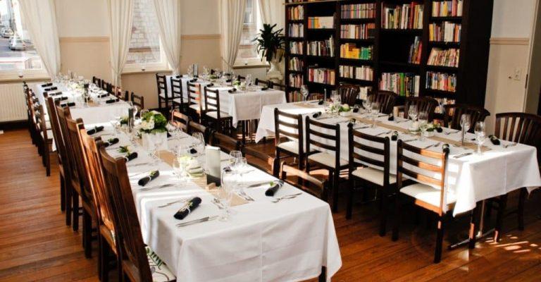 Vier lange Tafeln stehen vor Bücherregal und sind für ein Essen eingedeckt