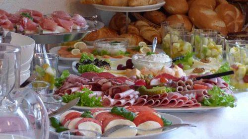 Frühstückbuffet mit Tomate-Mozzarella, Salami, Aufstrichen, Croissants und Brötchen