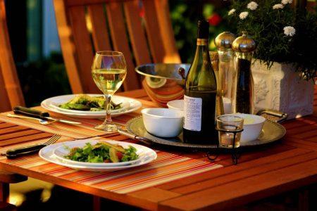 Bistrotisch mit Vorspeisensalat und Flasche Rotwein