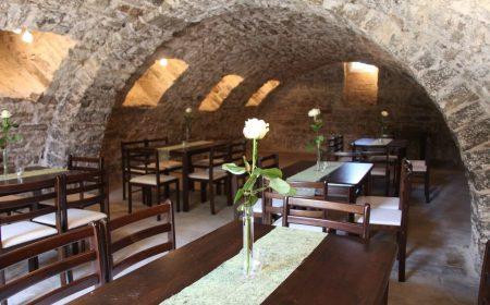 Im Gewölbekeller mit Rundbogen finden fünf lange Tafeln aus Holz Platz