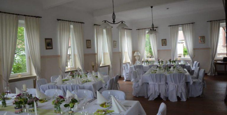 Vier viereckige Tische mit Gedeck sind im großen Salon angeordnet