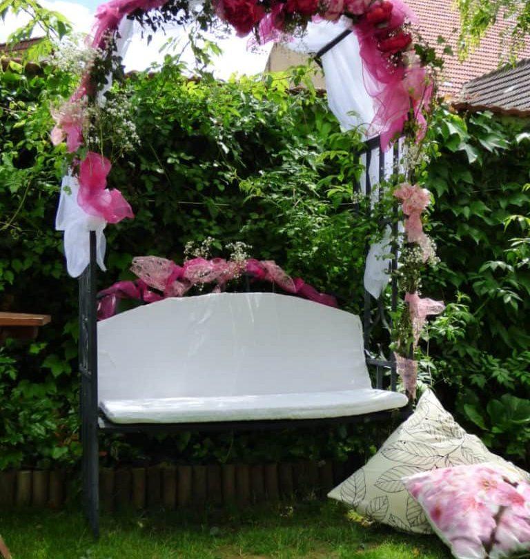 Eine mit rosa und weißen Stoffrosen verzierte Hollywoodschaukel steht im Grünen vor einer Hecke