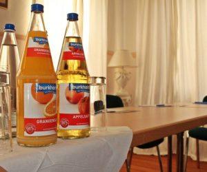 Angebot an Getränkeverpflegung mit Apfelsaft in einer Glasflasche