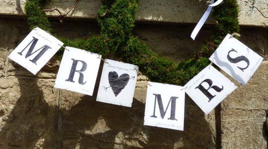 Am Treppenaufgang mit Hof des Landhauses hängen Schilder mit der Aufschrift Mr. und Mrs.