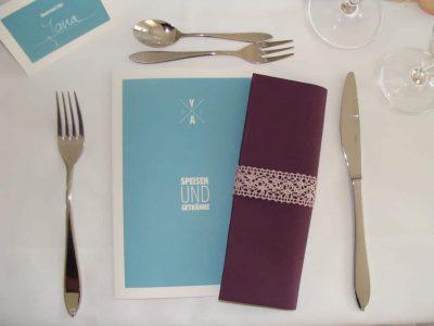 blaue Speisekarte und lila Serviette zwischen Essensbesteck