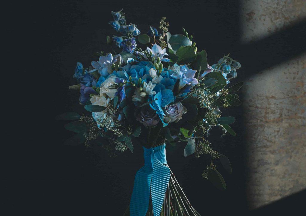 Brautstrauß mit blauen Hortensien, weißen Rosen und Bambus wird von blauem Band zusammengehalten
