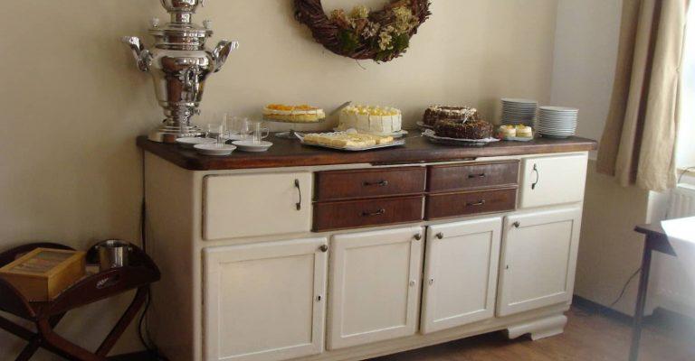 kleines Kuchenbuffet auf dekoriertem Sideboard