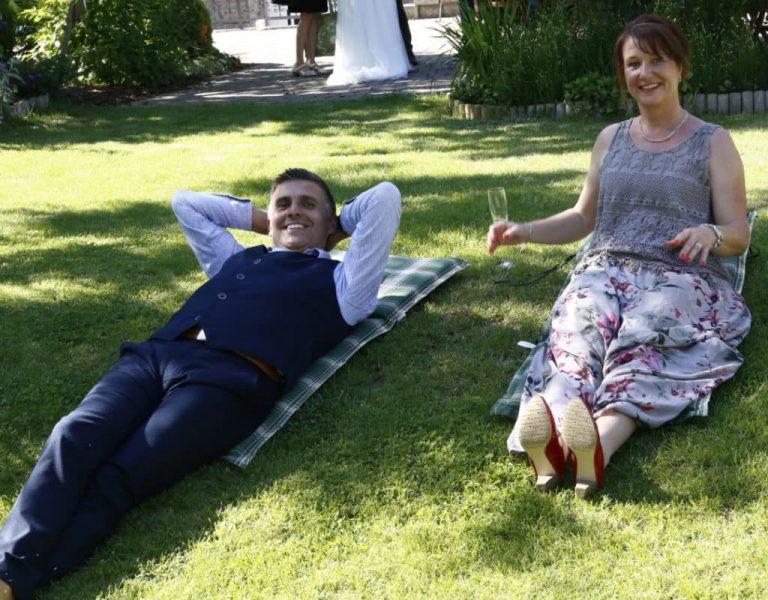 lachende Gäste liegen auf der grünen Wiese im Garten